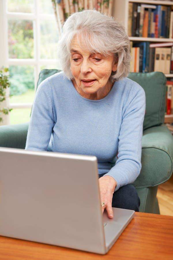 Mulher sênior que usa o portátil em casa foto de stock