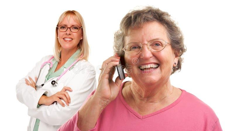Mulher sênior que usa o telefone de pilha com doutor fêmea foto de stock