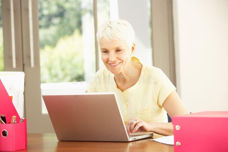 Mulher sênior que usa um portátil em casa fotos de stock
