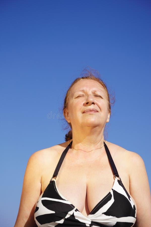 A mulher sênior relaxa na praia imagens de stock