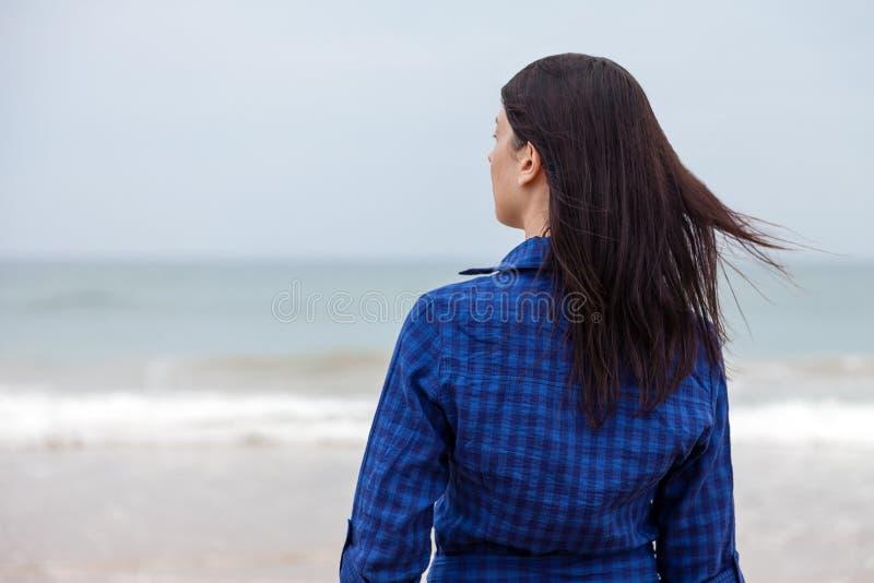 Mulher só e deprimida que está na frente do mar imagens de stock