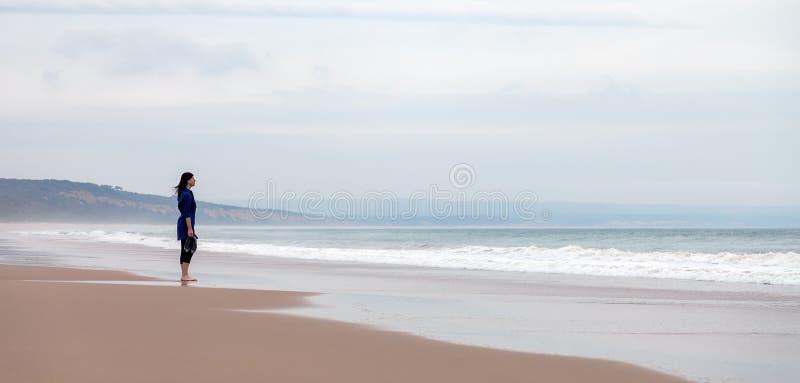 Mulher só e deprimida que está na frente do mar fotografia de stock royalty free