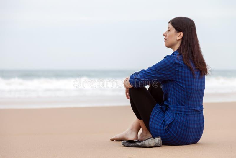 Mulher só e deprimida que senta-se na areia de uma praia abandonada imagens de stock royalty free
