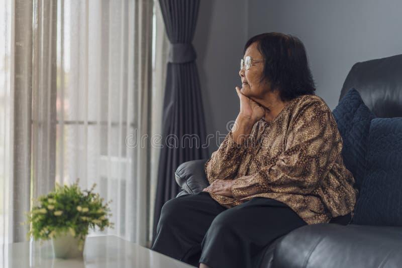 Mulher só idosa que senta-se no sofá na sala de visitas fotografia de stock royalty free