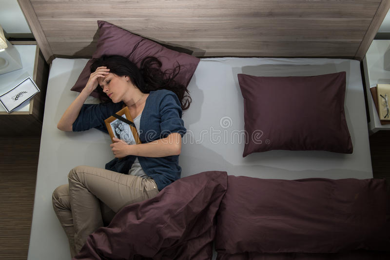 Mulher só na cama que falta o marido inoperante fotos de stock royalty free