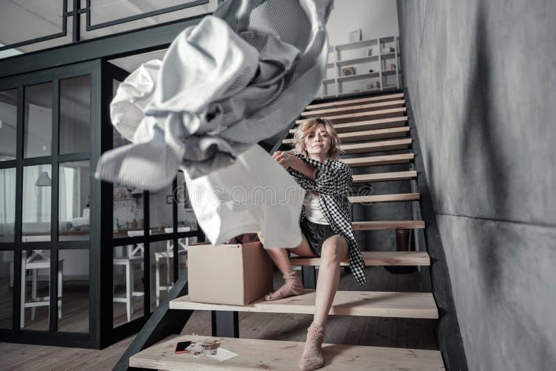 Mulher só que senta-se em escadas em casa e na roupa de jogo imagens de stock