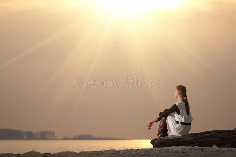 Mulher só que senta-se na costa do lago fotografia de stock