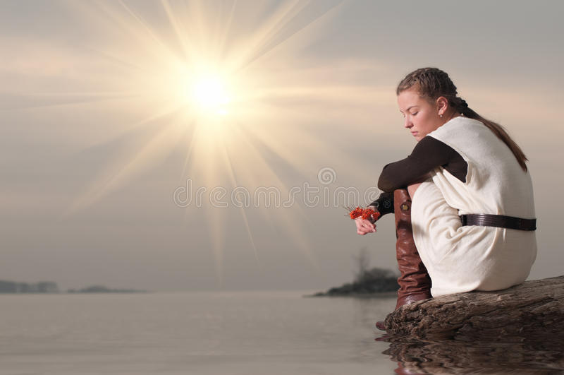 Mulher só que senta-se na costa do lago imagem de stock royalty free