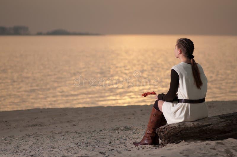 Mulher só que senta-se na costa do lago fotos de stock royalty free