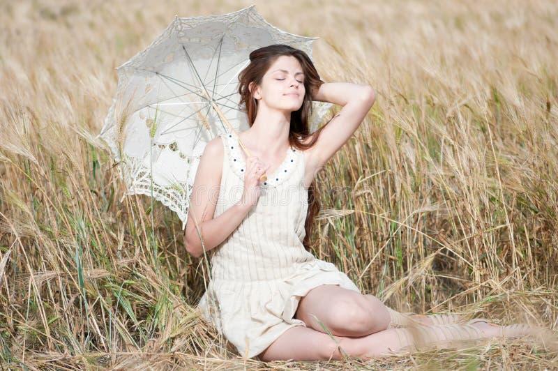 Mulher só que senta-se no campo de trigo fotos de stock royalty free