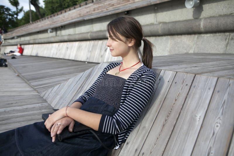 Mulher só que senta-se pelo rio imagem de stock