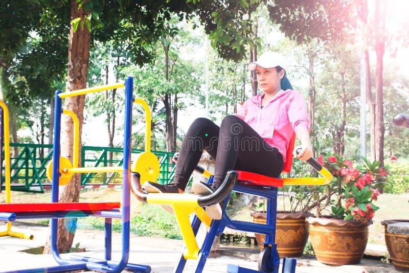 Mulher 40s asiática que exercita com equipamentos de treinamento no publi foto de stock royalty free