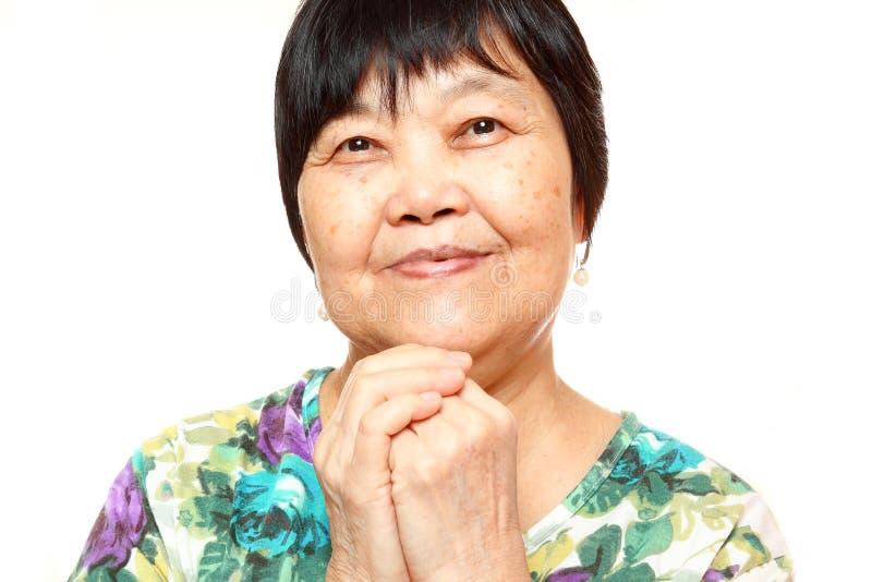 Mulher 60s asiática superior feliz fotografia de stock