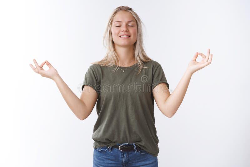 Mulher 25s atrativa nova calma com cabelo louro que inalam os olhos do fim do ar fresco e sorriso aliviado e feliz foto de stock