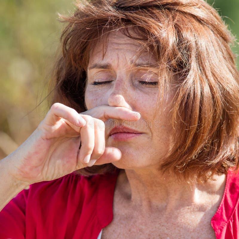 Mulher 50s bonita que tem alergias da febre de feno no campo fotos de stock royalty free