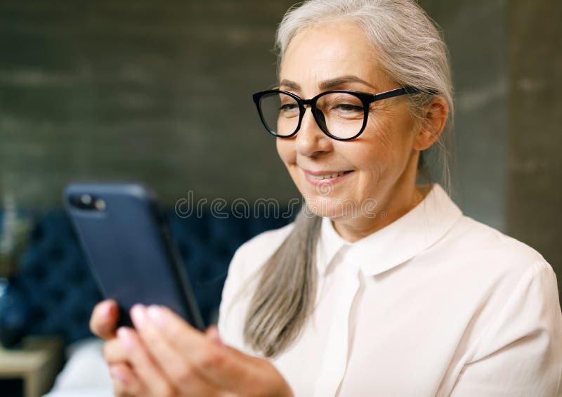 Mulher s?nior que usa o smartphone fotos de stock royalty free