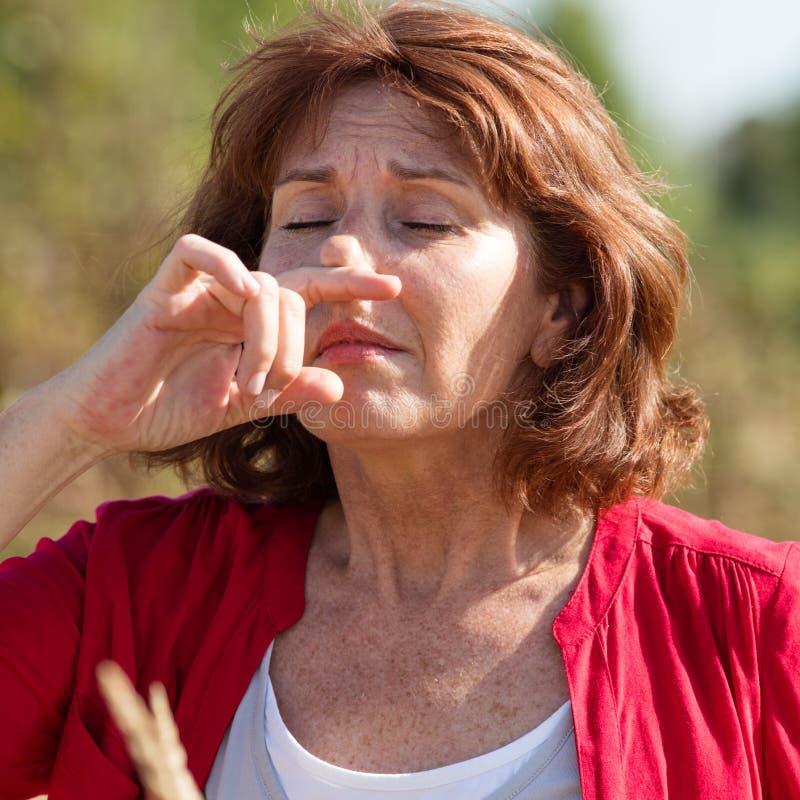 mulher 50s que tem alergias da febre de feno no campo imagens de stock