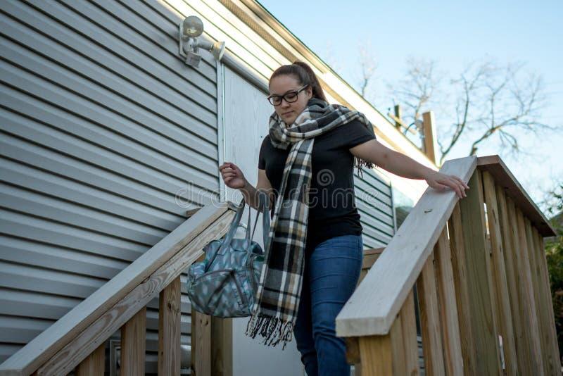 A mulher sae em casa com o saco drapejado sobre seu braço foto de stock royalty free