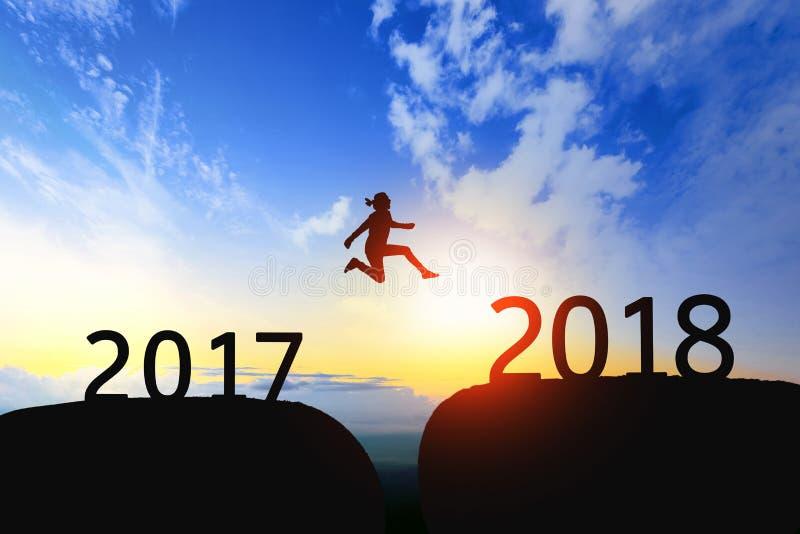 A mulher salta com a diferença entre 2017 a 2018 no por do sol fotografia de stock