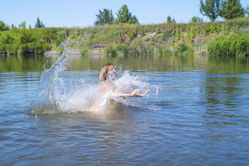 A mulher salta como peixes na água do lago, nada, aprecia passar o tempo em férias de verão A mulher salta no rio imagem de stock
