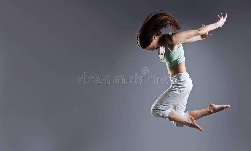 A mulher salta Dança da menina da beleza no fundo cinzento fotos de stock royalty free