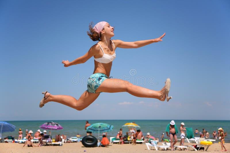 A mulher salta em uma praia foto de stock