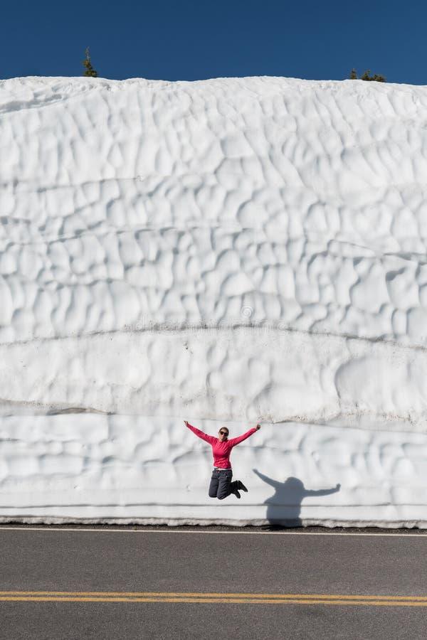 A mulher salta na frente da tração alta da neve fotos de stock