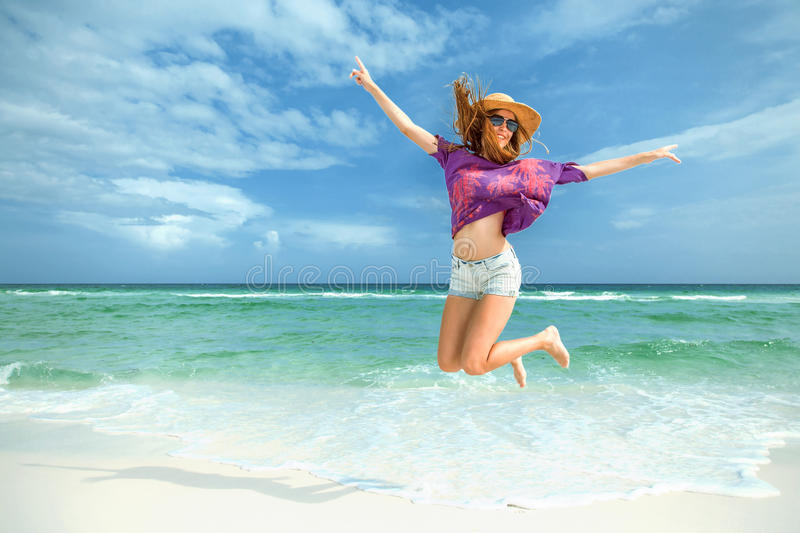 A mulher salta para a alegria na praia branca da areia imagem de stock royalty free