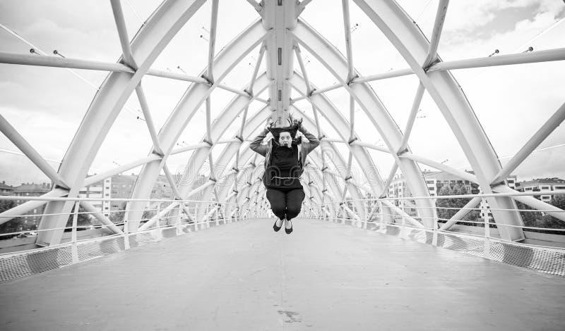 A mulher salta a ponte fotografia de stock royalty free