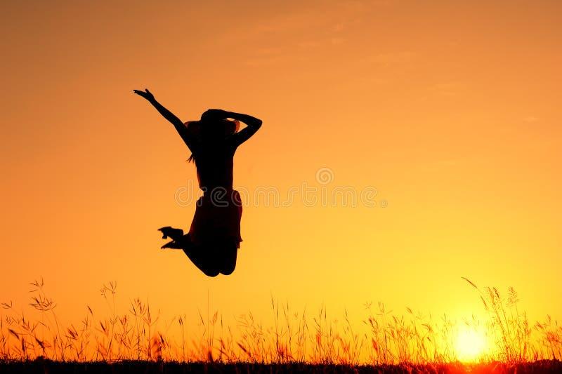 A mulher saltam e a silhueta do por do sol fotografia de stock