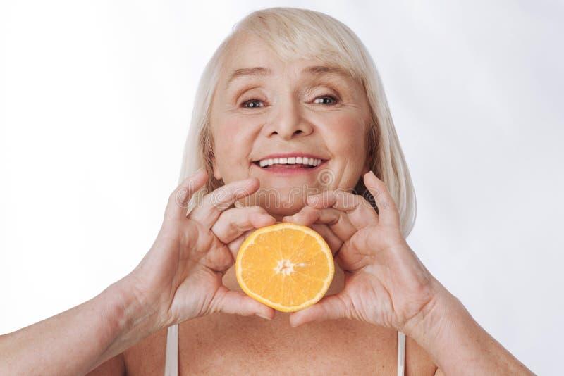 Mulher satisfeita agradável que guarda uma laranja imagens de stock