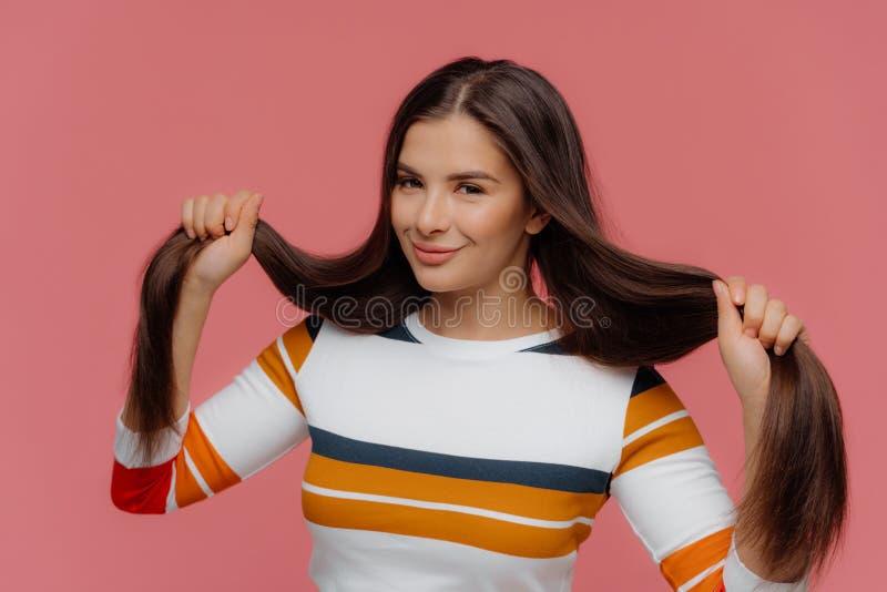 A mulher satisfeita guarda seu cabelo importado longo, sorrisos delicadamente, vestido na ligação em ponte listrada branca, olha  foto de stock royalty free
