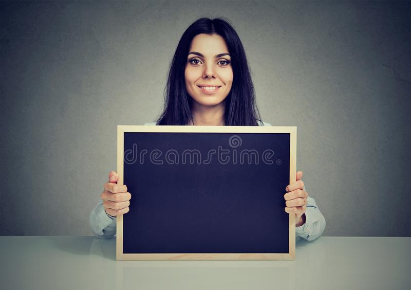 Mulher satisfeita que mostra o quadro-negro vazio fotografia de stock