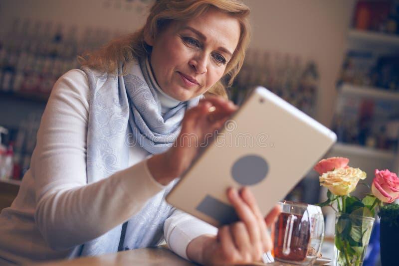 Mulher satisfeito que trabalha na tabuleta digital fotografia de stock royalty free
