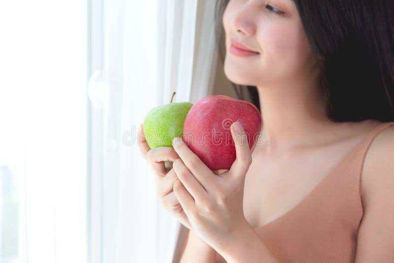 Mulher saudável alegre comendo a maçã verde e vermelha imagem de stock