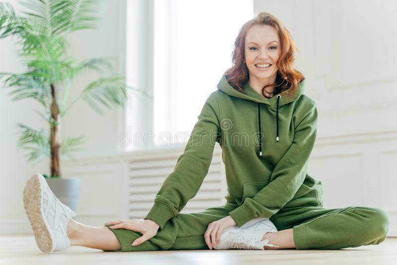 A mulher saudável ativa estica no assoalho, veste o fato de esporte verde, faz exercícios, tem a expressão contente, faz o exercí imagens de stock royalty free
