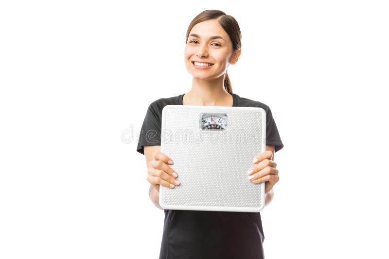 Mulher saudável bonita que sorri ao mostrar a escala do peso fotografia de stock