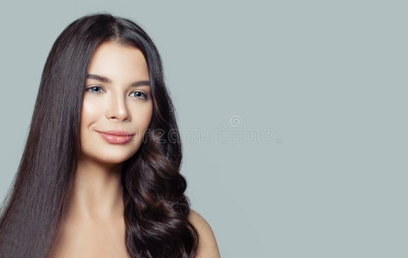 Mulher saudável com cabelo reto e encaracolado no fundo azul com espaço da cópia Denominação do cabelo e conceito dos cuidados ca imagem de stock
