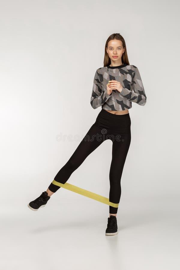 A mulher saudável com o bom físico que faz o esticão dá certo com faixas elásticas fotografia de stock royalty free