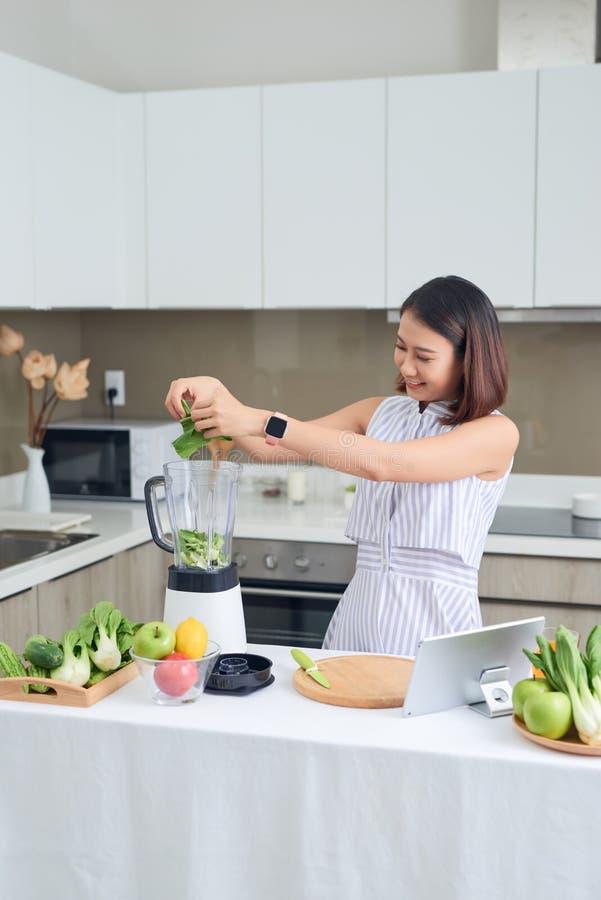 Mulher saudável da Ásia gosta de fazer limpadores de detox de legumes verdes e suavização de frutas verdes com liquidificador em  foto de stock royalty free