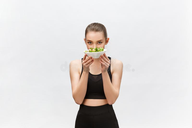 Mulher saudável da aptidão que come a salada e estar, isoladas no fundo branco fotos de stock