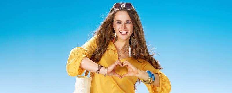 A mulher saudável de sorriso no litoral que mostra o coração deu forma às mãos foto de stock royalty free