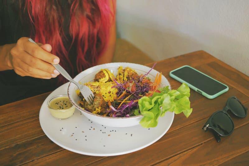 Mulher saudável do estilo de vida que come bolas do Falafel do vegetariano com salada verde fresca no restaurante do vegetariano imagens de stock