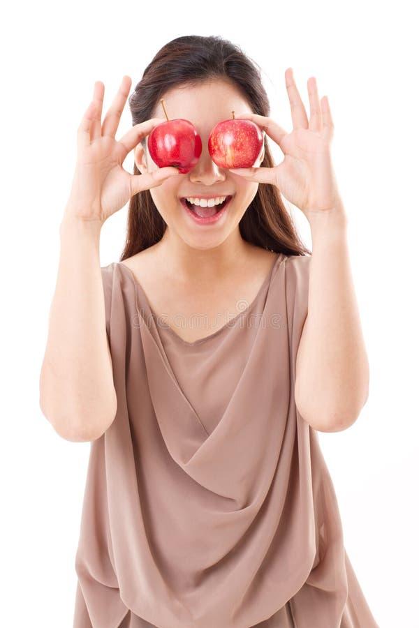 Mulher saudável e brincalhão que cobre seus olhos com as duas maçãs vermelhas imagem de stock