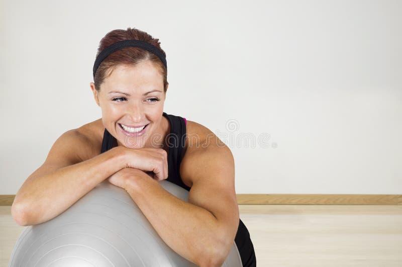 Mulher saudável feliz da aptidão que descansa em uma bola do exercício fotos de stock royalty free