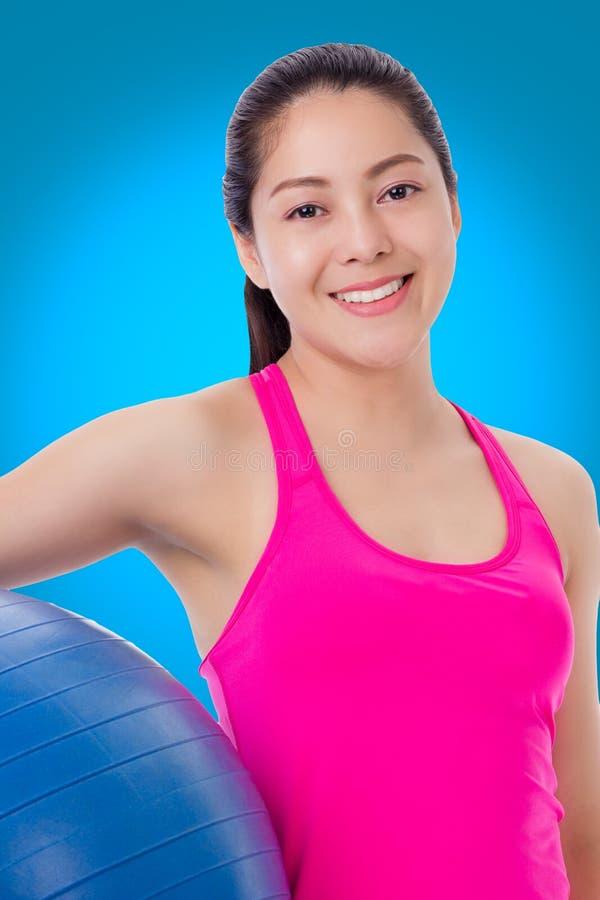 Mulher saudável - menina que sorri e que guarda a bola da aptidão, parte traseira do azul foto de stock royalty free