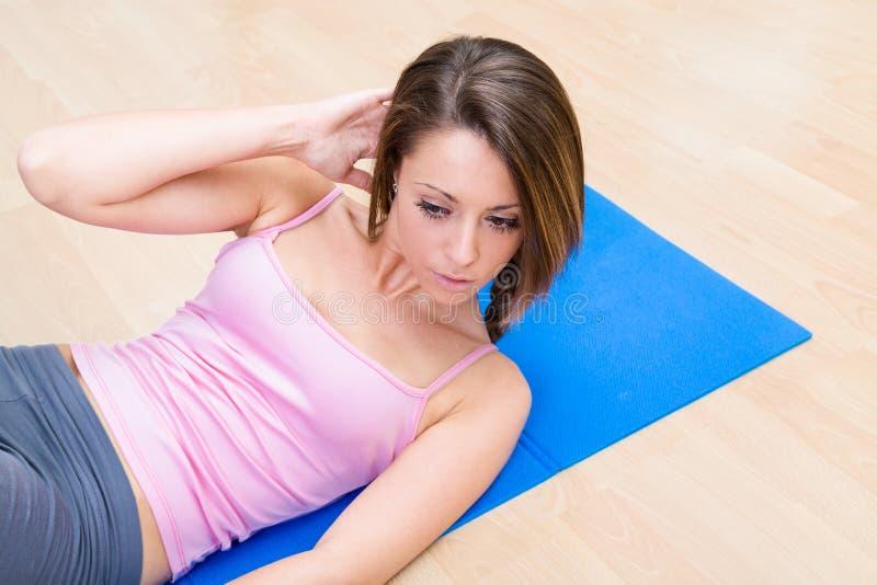 Mulher saudável nova em exercícios do Abs imagens de stock royalty free