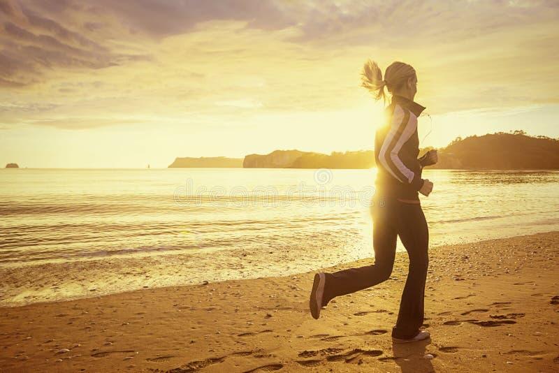 Mulher saudável que corre na praia no por do sol fotos de stock