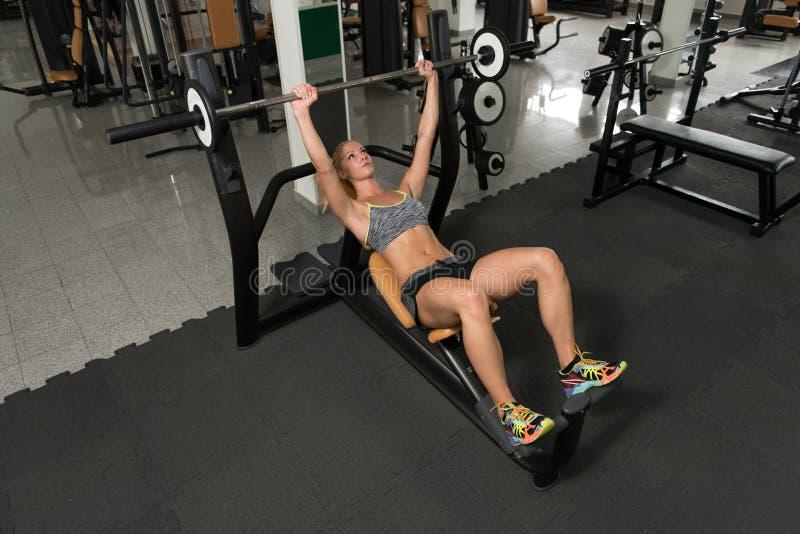 Mulher saudável que faz o exercício da imprensa de banco para a caixa imagens de stock