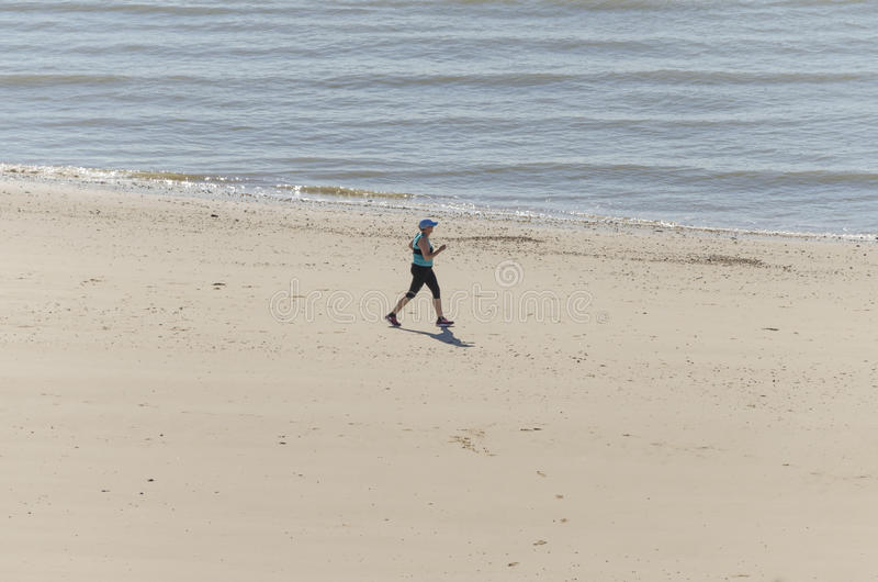 Mulher saudável que funciona na praia fotografia de stock royalty free